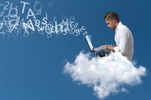 Młody przedsiębiorca siedzący w chmurze i pracujący na kompputarze