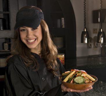 młoda kobieta w restauracji trzymająca tajskie danie