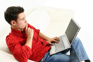 Młody mężczyzna rozwiązujący testy przez internet