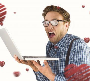 Młody mężczyzna trzymający laptopa w rękach