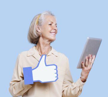 """Starsza pani z tabletem w ręku oraz znaczkiem """"lubię to"""""""