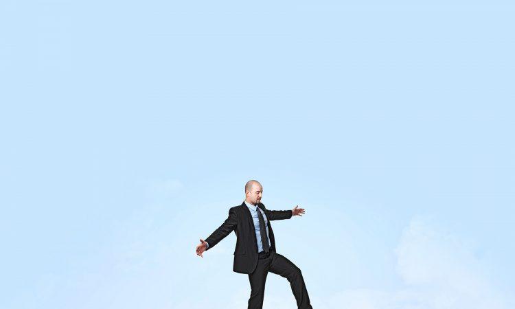 Przedsiębiorca balansujący na górze pieniądzy