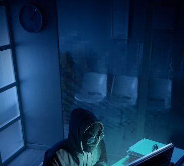 Cyberprzestępca siedzi przed komputerem
