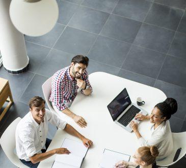 Młodzi ludzie pracujący wspólnie przy biurku w biurze