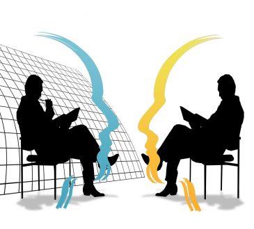 dwóch ptrzedsiębiorców siedzących na przeciwko siebie na krzesłach i negocjujących