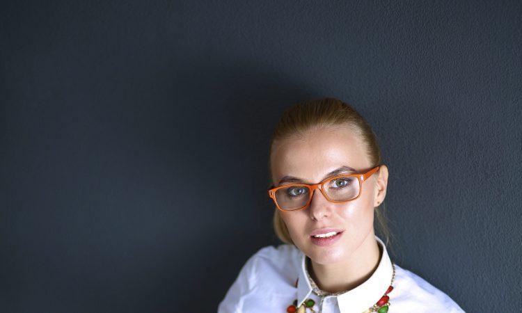 Młoda kobieta w białej bluzce i okularach siedzi przed laptopem