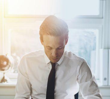 Mężczyzna w białej koszuli uzupełnia dokumenty siedząc przy biurku